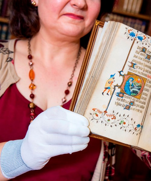Librarian Susan Taylor with Late 14th Century Book of Hours