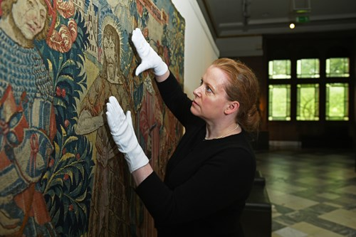 Conservator with tapestry at Kelvingrove