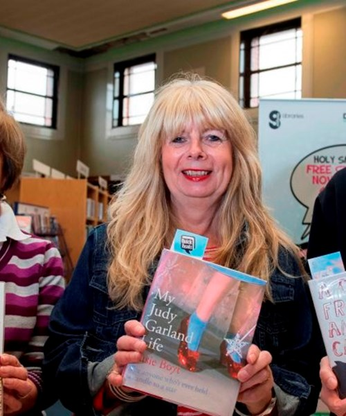 Three members of the book club holding up books