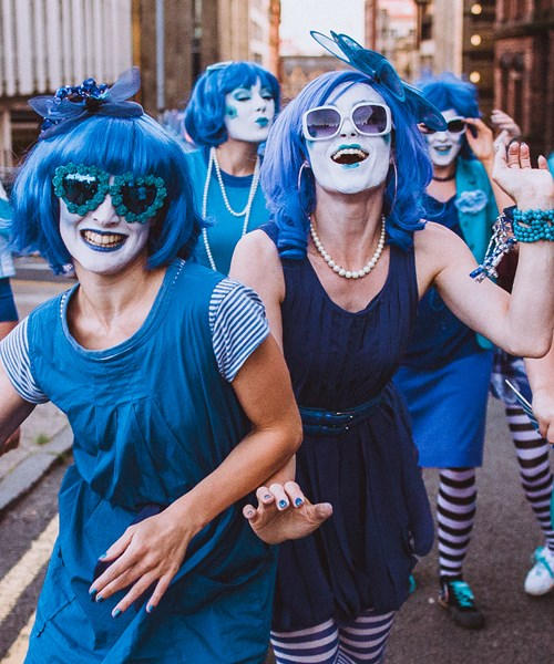 A group of performers, all dressed in bright blue and wearing blue wigs, at Merchant City Festival